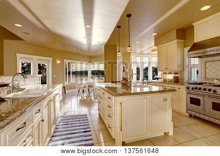 Large Luxury Kitchen Room In Beige Colors With Granite Counter Tops And Kitchen Island