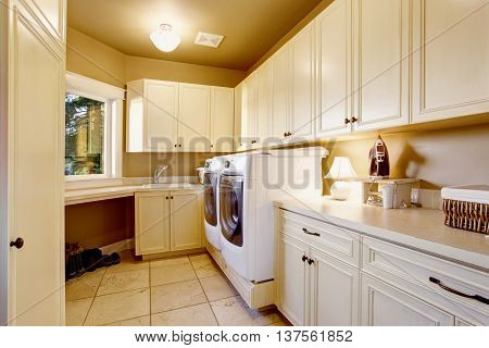 White Laundry Room Interior With Tile Floor And Cabinets.