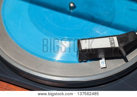 above view of headshell of old turntable on blue flexi disc