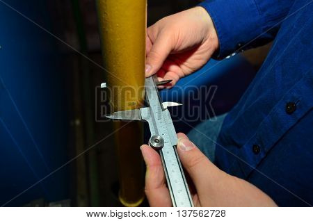 A craftsman measures the tube diameter with a caliper