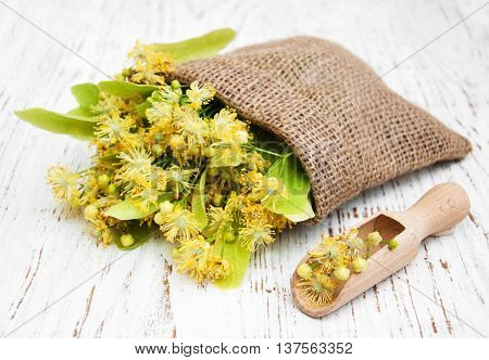 linden flowers in canvas bag on a old wooden background