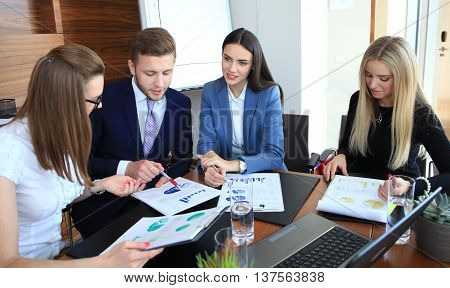 startup business team on meeting in modern bright office interior brainstorming working on laptop and tablet computer