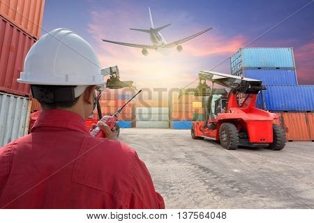 Worker control Containers with forklift at yard beautiful sky at dusk with plane background
