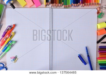 Open Notebook In Center With School Material Around