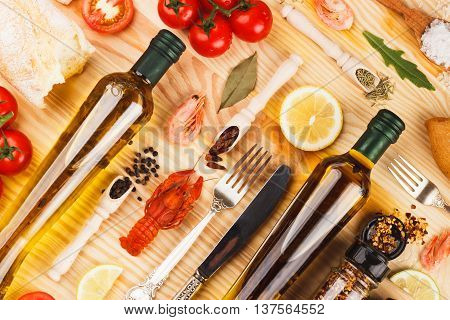Different Spices And Silverware Between Glass Bottles Of Olive Oil