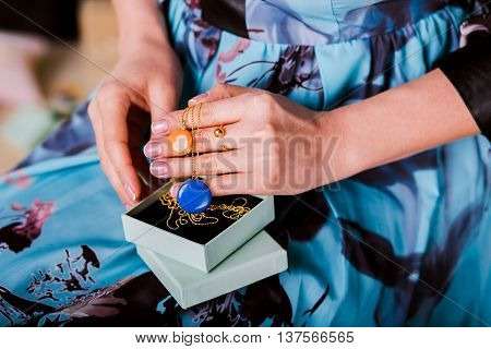 Woman showing beautiful Jewelry necklace with enamel Jewelry. closeup hands. Concept of luxurious and wealth life