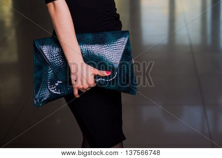 Lady's bag. Closeup of green leather handbag in hand of modern woman. fashion accessory. Female fashion. Elegant clothes.