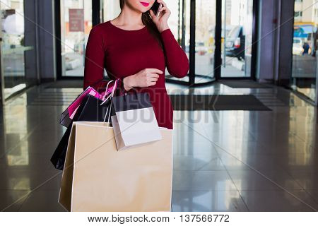 stylish shopper holding lot of handbags. Shopping center shopping go shopping.
