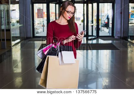 Happy shopper. fashionable woman holding many shopping bag and using cell phone.