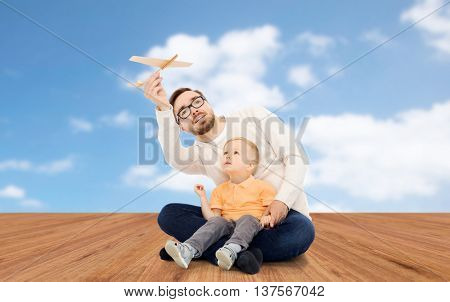 family, childhood, fatherhood, leisure and people concept - happy father and little son playing with toy airplane over blue sky and wooden floor background