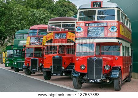 WEYBRIDGE SURREY UK - AUGUST 18: A line of vintage red and green vintage buses outside the transport museum at Brooklands Motor Museum Weybridge in 2013.