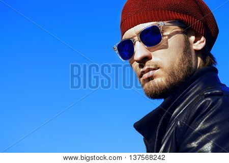 Portrait of a handsome young man in a leather jacket and sunglasses over blue sky background. Men's beauty, fashion.