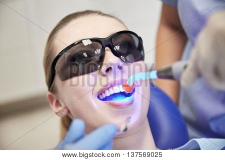 people, medicine, stomatology and health care concept - close up of woman patient in protective eyeglasses or goggles with dental curing light treating teeth at dental clinic office