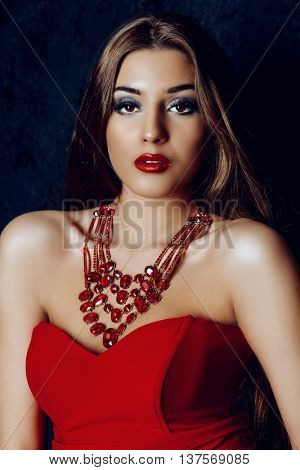 Beautiful sexy woman with evening make-up and magnificent long hair wearing red dress. Luxurious style. Jewellery. Eyelash extensions, false eyelashes. Red lipstick.