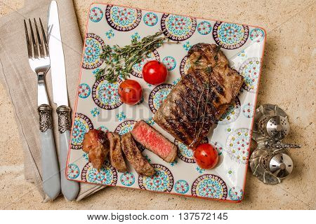 Sliced medium rare grilled Beef steak Ribeye with grilled cherry tomatoes on plate on wooden background,  top view