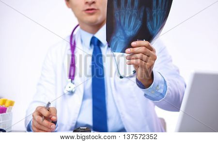young doctor examines an x-ray while sitting at the table.