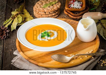 Pumpkin and carrot soup with cream and seasoning in white bowl  on wooden background
