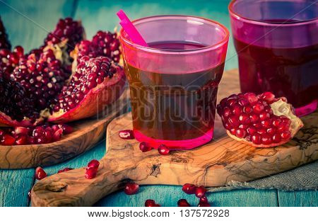 pomegranate juice  and ripe red pomegranate fruit on blue wooden table