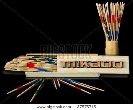 3D illustration of boxes of the game of mikado with wooden text Mikado and wooden sticks on a black background with reflections
