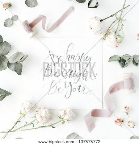 inspirational quote be happy be bright be you written in calligraphy style on paper with pink roses and eucalyptus branches on white background. flat lay top view