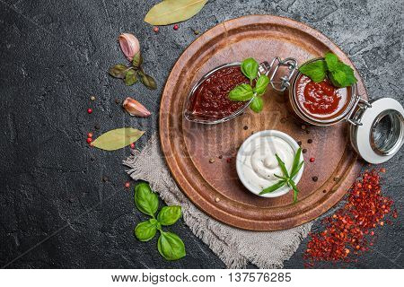 Various dip sauces on black background, top view