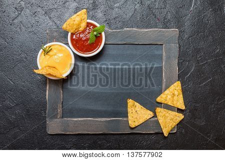 Mexican nacho with sauces and chalk board on black background, top view, copy space