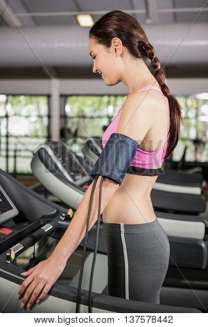 Woman at gym exercising on treadmill with mobile on armband