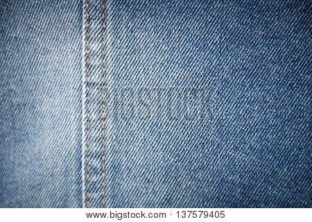 Blue denim texture background with seam on the left