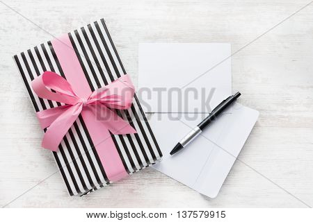 Empty greeting card. Wrapped gift, envelope and pen on a white wood background.