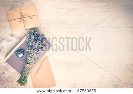 Lavender bouquet laid over an old book a wrapped gift box a kraft paper envelope and a silver heart on a white wooden background. Vintage style.
