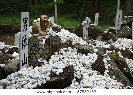 Heap of white pebble stones with religious wishes in the Japanese temples (Shinto shrines) as a symbol of Eastern traditions, Superstitions, Iconography and   religion.