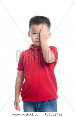 Portrait of cute smiling little boy closed one eye with his hand in studio