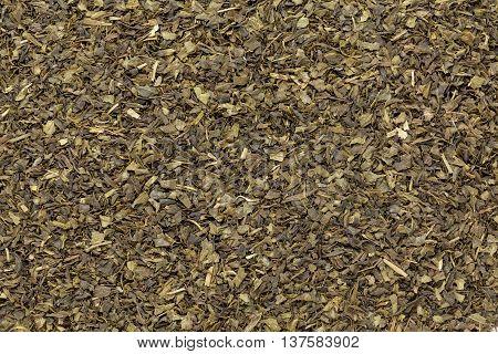 Organic Green tea (Camellia sinensis) Tea bag cut, dried leave. Macro close up background texture. Top view.