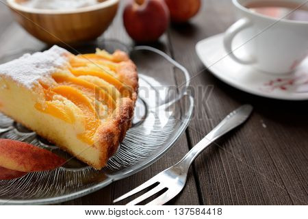 A slice of fresh peach pie sprinkled with sugar on a wooden background