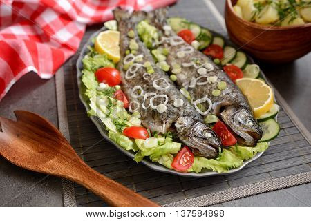 Roasted trout with vegetable and potatoes on a plate