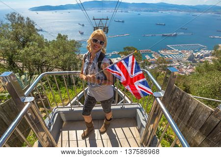 Happy tourist woman holding an English flag. On background the cable car that leads to Gibraltar Rock. Gibraltar is a British colony that is located at southern end of Iberian Peninsula.