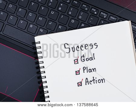 Handwriting word Success Goal Plan Action on blank notebook with laptop keyboard (Top view)