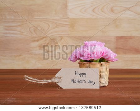 Sweet pink Carnation flower in the basket and handwriting Happy Mother's Day on brown label paper
