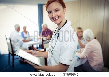 Portrait of a nurse with tablet computer in the retirement house