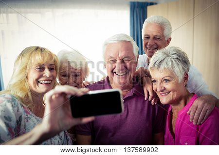 Group of seniors doing a selfie with a smartphone in the retirement house