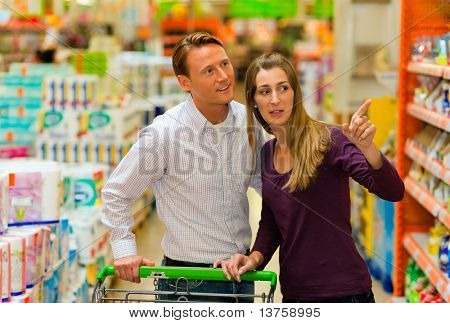 Paar in einem Supermarkt einkaufen, ausgestattet mit einem shopping Warenkorb kaufen Lebensmittel und andere Sachen, die