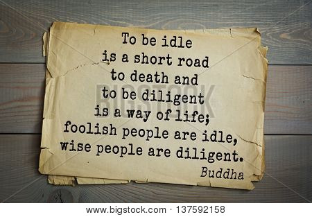 Buddha quote on old paper background. To be idle is a short road to death and to be diligent is a way of life; foolish people are idle, wise people are diligent.