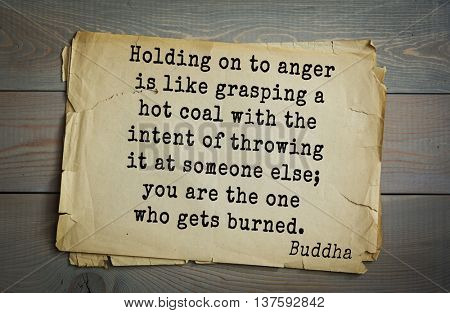Buddha quote on old paper background. Holding on to anger is like grasping a hot coal with the intent of throwing it at someone else; you are the one who gets burned.