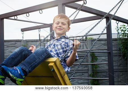 Little redheaded boy is swinging on the seesaw in the yard