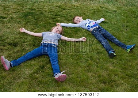 Little children rare laying on the lawn arms and legs outstretched