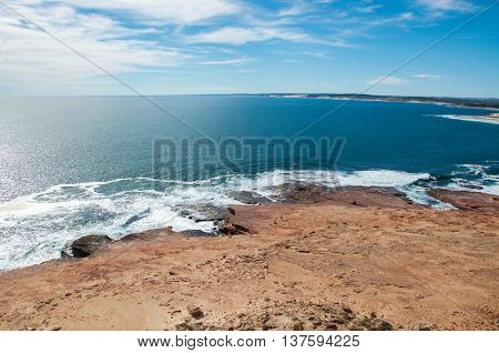 Scenic views at Red Bluff beach of the turquoise Indian Ocean waters with sandstone rock under a blue sky on the coral coast in Kalbarri, Western Australia.