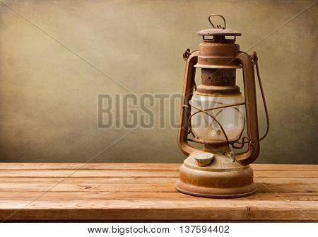 Vintage kerosene lamp on wooden table over grunge background