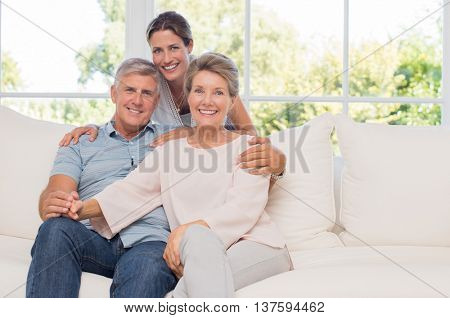 Portrait of senior couple sitting on couch with daughter. Elderly couple with daughter looking at camera. Mature daughter embracing her senior parents from behind.