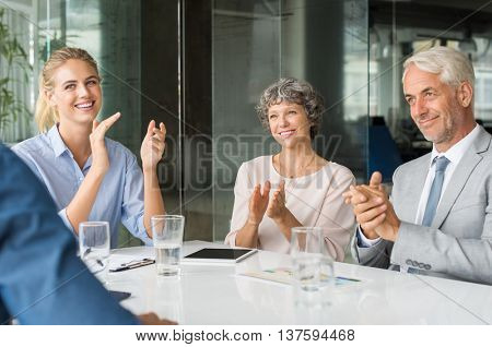 Group of business people meeting in corporate conference room, applauding at a coworker during his presentation. Business group greeting employee with clapping and smiling.