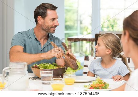 Happy father serving salad to daughter. Small young family enjoying lunch at dining table. Daughter asking father to serve food.